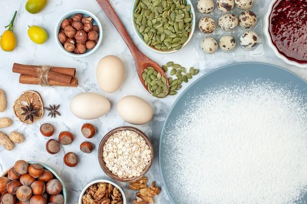 Vista superior farinha branca dentro do prato com sementes de nozes e ovos na massa de noz branca cozer comida foto bolo de frutas geléia