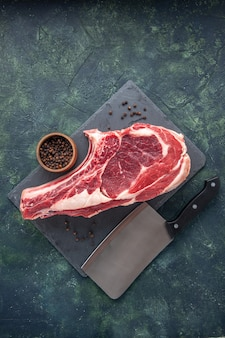 Vista superior fatia de carne fresca carne crua com pimenta em fundo escuro açougueiro foto animal cor de frango comida
