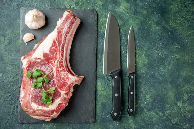 Vista superior fatia de carne fresca com facas em fundo azul escuro cozinha animal vaca comida carne de açougueiro cor de frango Foto gratuita
