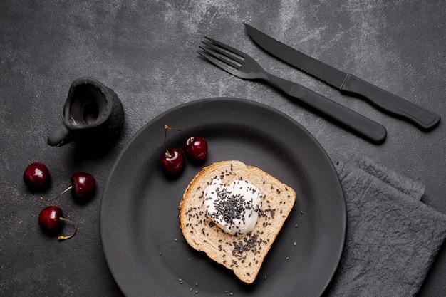 Vista superior fatia de pão com creme e arranjo de cerejas