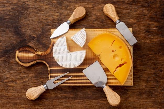 Vista superior fatia de queijo com ferramentas sobre uma mesa