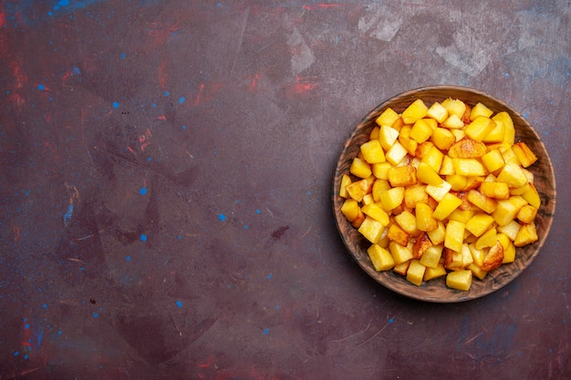 Vista superior fatiada de batatas cozidas dentro de um prato marrom no escuro