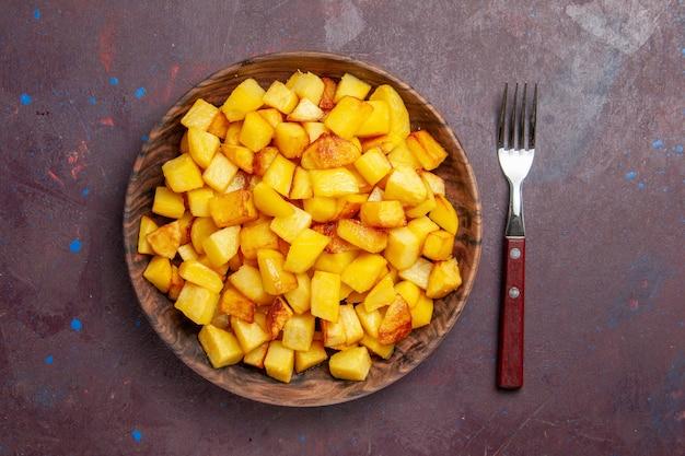 Vista superior fatiada de batatas cozidas dentro do prato no escuro