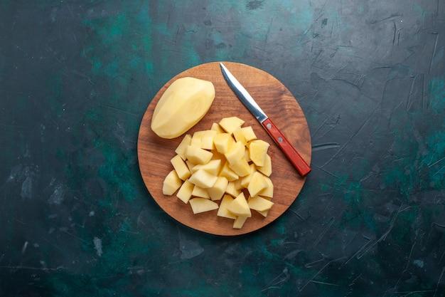Vista superior fatiada de batatas frescas com faca no fundo azul escuro