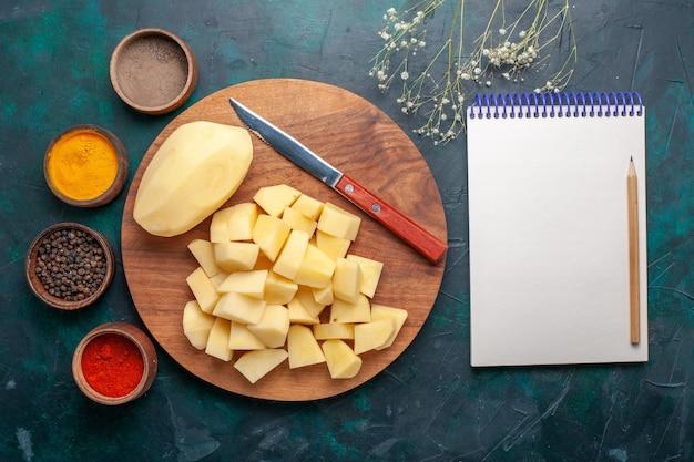 Vista superior fatiada de batatas frescas com temperos e bloco de notas em fundo azul escuro
