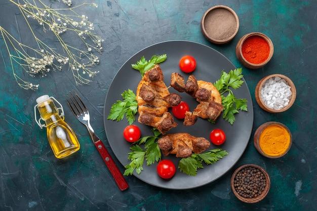 Vista superior fatiada de carne cozida com óleo de tomate cereja verde e temperos em fundo azul