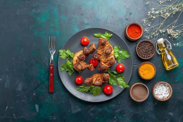 Vista superior fatiada de carne cozida com tomate cereja dentro do prato e com temperos em fundo azul