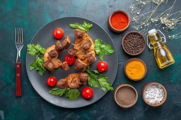 Vista superior fatiada de carne cozida com tomate cereja dentro do prato e com temperos no fundo azul escuro