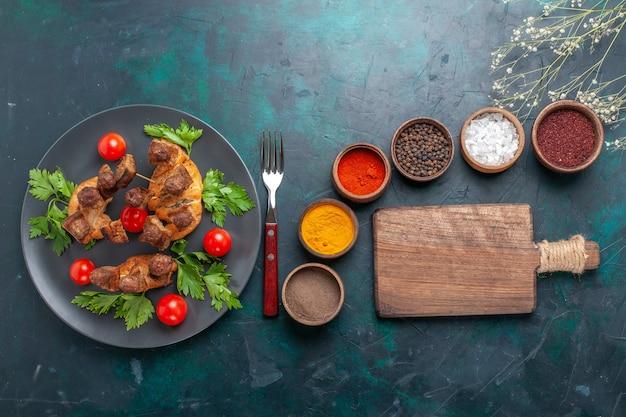 Vista superior fatiada de carne cozida com tomate cereja e temperos diferentes em fundo azul