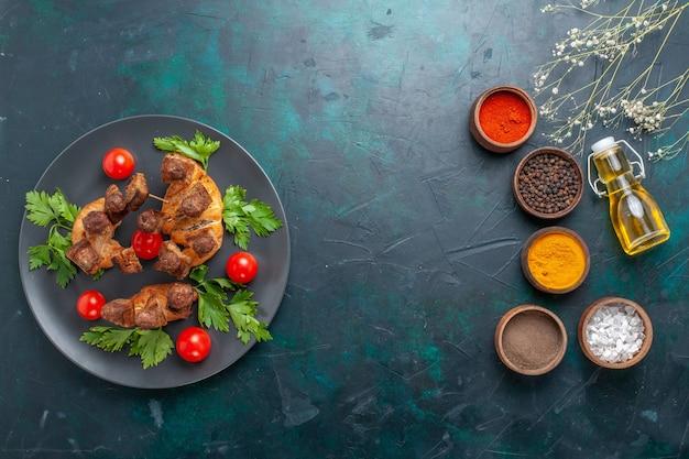 Vista superior fatiada de carne cozida com tomate cereja e temperos em fundo azul