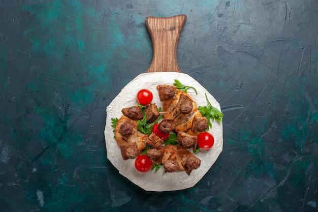 Vista superior fatiada de carne cozida com tomates-cereja verdes dentro de pita em fundo azul escuro