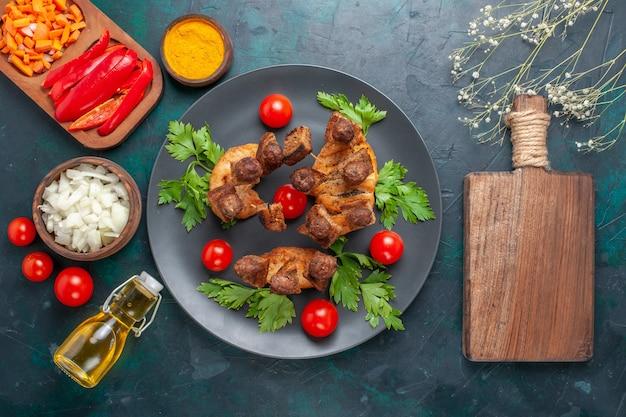 Vista superior fatiada de carne cozida com tomates cereja verdes e azeite de oliva no fundo azul