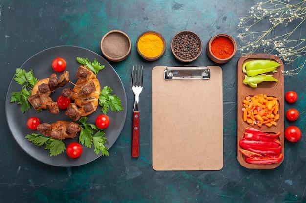Vista superior fatiada de carne cozida com verduras e tomate cereja dentro do prato com temperos em fundo azul escuro