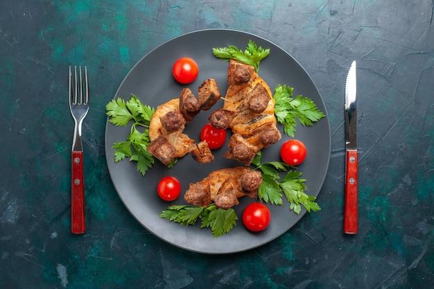 Vista superior fatiada de carne cozida com verduras e tomate cereja dentro do prato no fundo azul escuro
