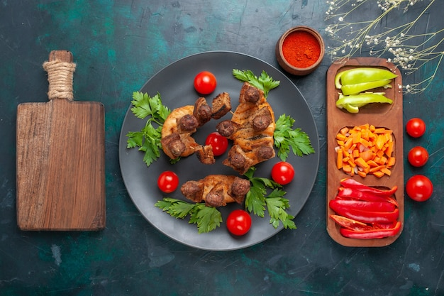 Vista superior fatiada de carne cozida com verduras e tomate cereja dentro do prato no fundo azul