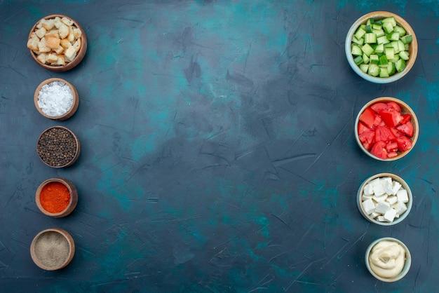 Vista superior fatiada de legumes frescos, pepinos e tomates, junto com temperos no fundo escuro refeição alimentar salada de legumes