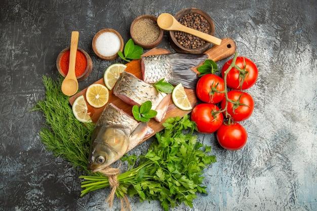 Vista superior fatiada de peixe fresco com limão e verduras em superfície clara
