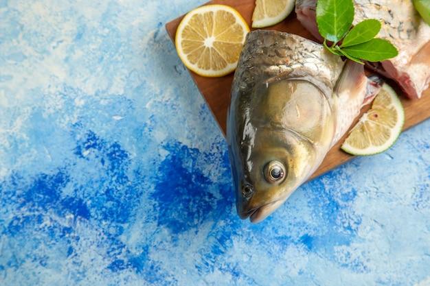 Vista superior fatiada de peixe fresco com rodelas de limão na superfície azul clara