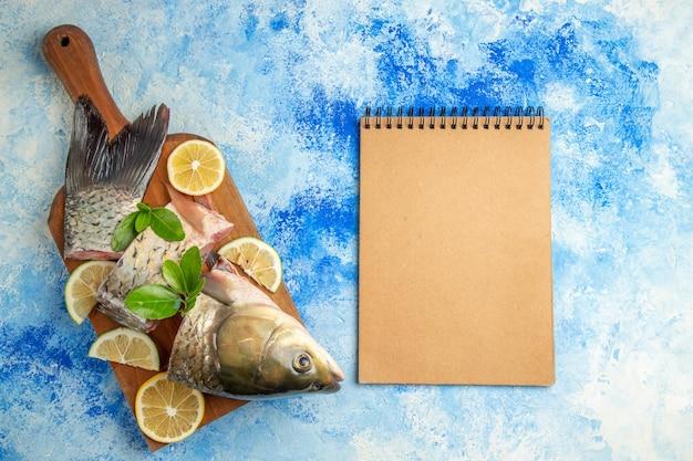 Vista superior fatiada de peixe fresco com rodelas de limão na superfície azul