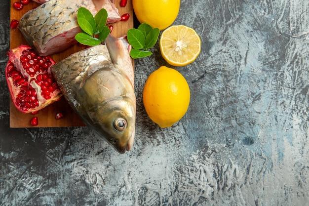 Vista superior fatiada de peixe fresco com romãs e limão na mesa leve