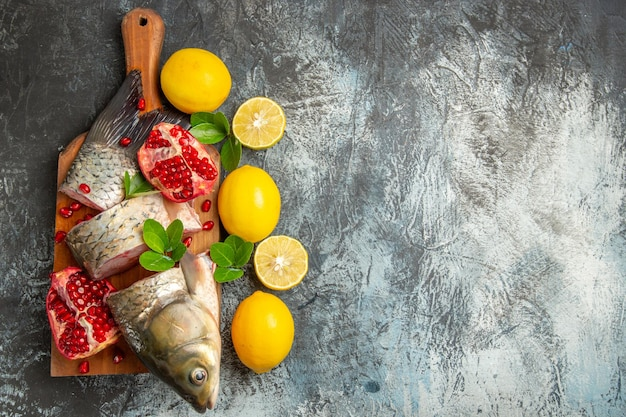 Vista superior fatiada de peixe fresco com romãs e limão na superfície clara