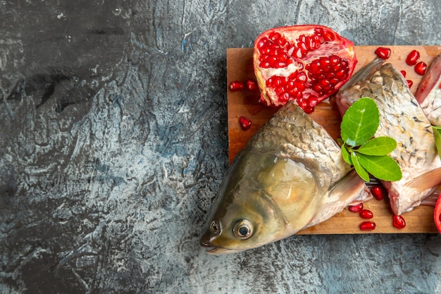 Vista superior fatiada de peixe fresco com romãs na superfície claro-escuro