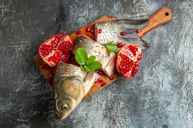 Vista superior fatiada de peixe fresco com romãs na superfície escura