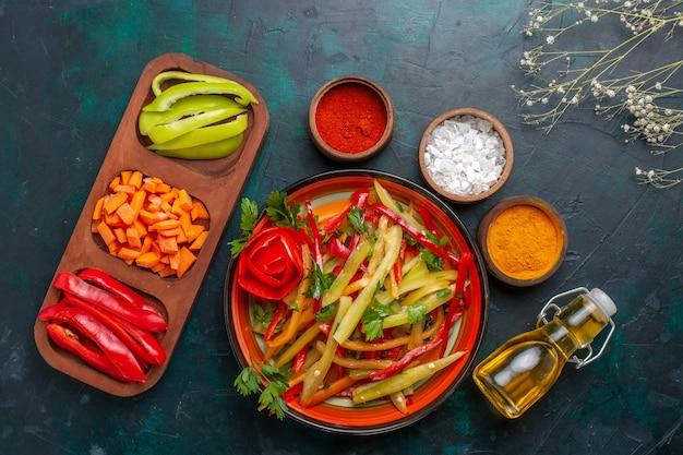Vista superior fatiada de pimentões com salada de temperos e azeite em fundo azul escuro