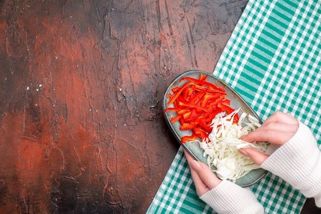 Vista superior fatiada de repolho com pimentão na mesa escura