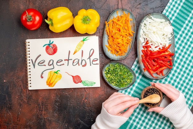 Vista superior fatiada de vegetais, cenoura, repolho e pimentão com verduras na mesa escura