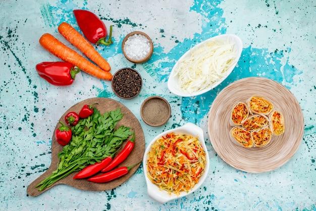 Vista superior fatiada de vegetais em fatias de massa com recheio saboroso, juntamente com cenouras verdes e pimentões vermelhos picantes na mesa azul brilhante comidinhas