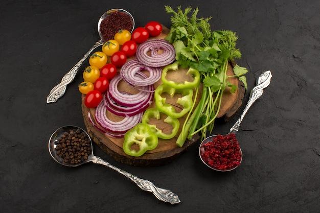 Vista superior fatiada legumes inteiros, como cebola verde tomate pimentão no fundo escuro