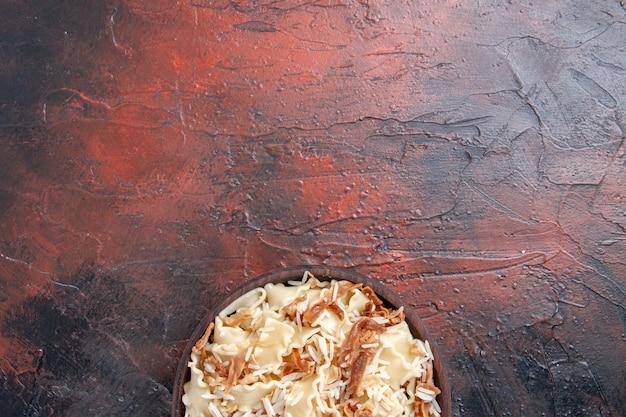 Vista superior fatiada massa cozida com arroz em prato de superfície escura farinha de massa