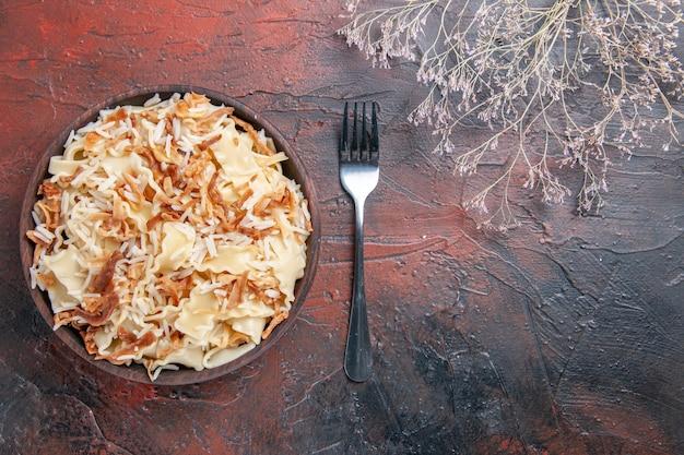 Vista superior fatiada massa cozida com arroz na superfície escura