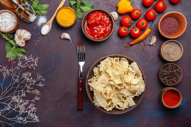 Vista superior fatiada massa crua com tomate e temperos em fundo escuro.