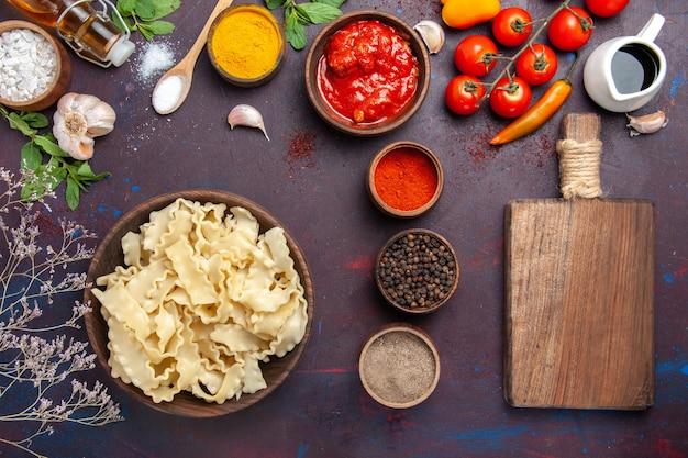 Vista superior fatiada massa crua com tomates vermelhos e diferentes temperos na mesa escura