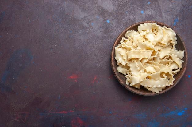 Vista superior fatiada massa crua dentro de um prato marrom em fundo roxo escuro
