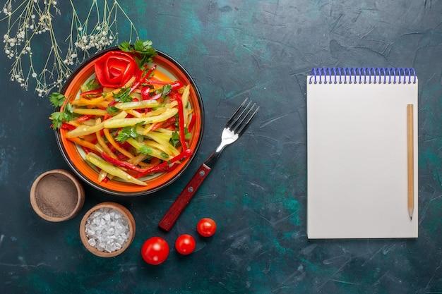 Vista superior fatiada saborosa salada saudável de pimentão com temperos e bloco de notas em fundo escuro