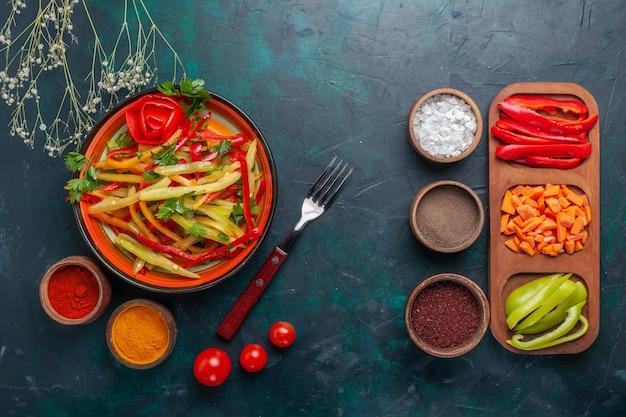 Vista superior fatiada saborosa salada saudável de pimentão com temperos e outros vegetais em fundo escuro