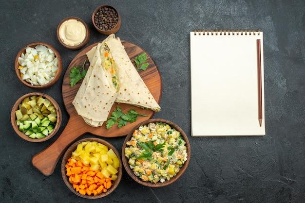 Vista superior fatiada sanduíche de salada shaurma com diferentes vegetais na superfície cinza