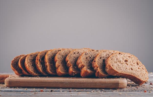 Vista superior fatiado de pão na tábua na mesa de madeira e superfície cinza