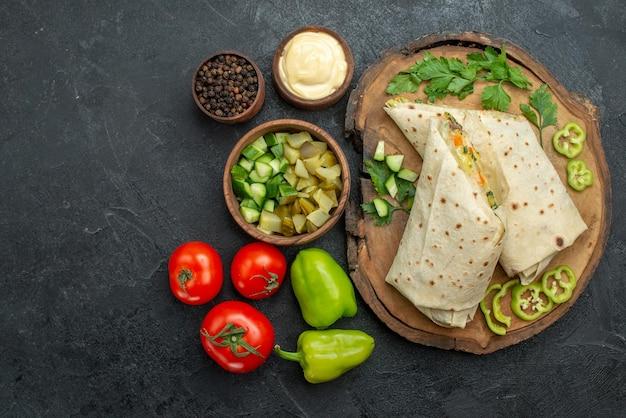 Vista superior fatiado delicioso sanduíche de salada shaurma com vegetais frescos na superfície cinza sanduíche de sanduíche de pão pita refeição