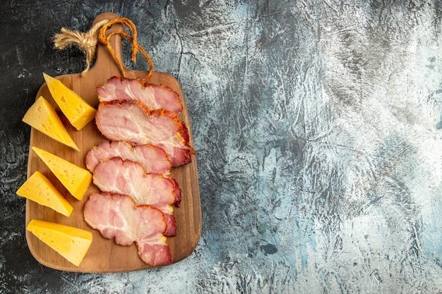 Vista superior fatias de carne fatias de queijo na tábua de corte em fundo cinza