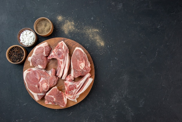 Vista superior fatias de carne fresca carne crua com temperos na refeição escura comida frescura vaca comida animal de cozinha