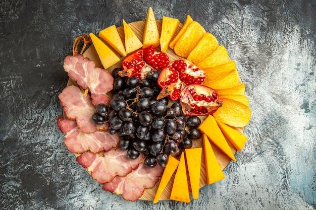 Vista superior fatias de carne, queijo, uvas e romã em uma tábua oval em uma superfície escura