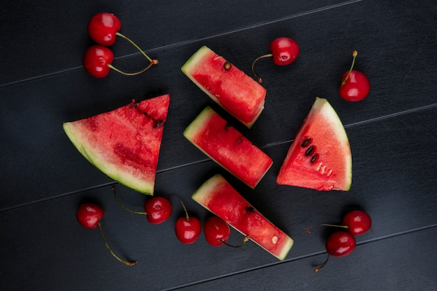 Vista superior fatias de melancia com cerejas em um fundo preto