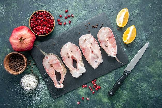 Vista superior fatias de peixe fresco na mesa escura carne frutos do mar prato de refeição do mar alimentos crus oceano pimenta água