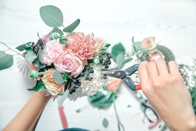 Vista superior fechar feminino corta flores em pé no balcão. organizando várias flores em moderno buquê fresco. copie o espaço. conceito profissional de floricultura, negócios, venda e produtos de floricultura