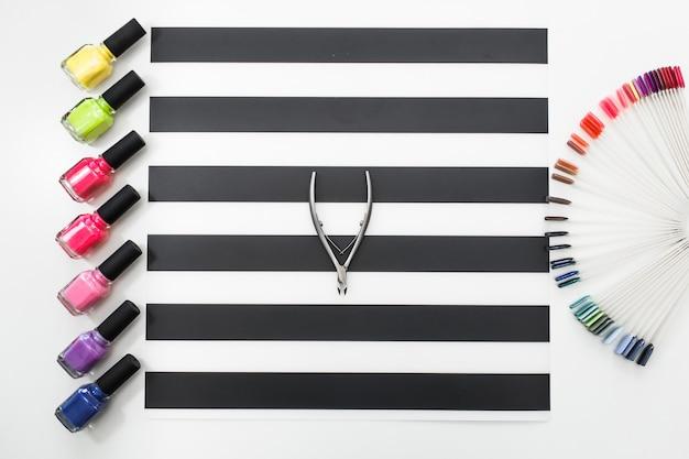 Vista superior fechar imagem de empurrador de cutícula e paleta de cores de esmaltes em cima da mesa