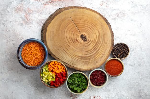 Vista superior feijão de laranja cru com temperos na superfície branca farinha de feijão merci ingrediente de vegetais